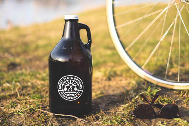 A 32 ounce Great Flats growler full of delicious beer next to a bicycle